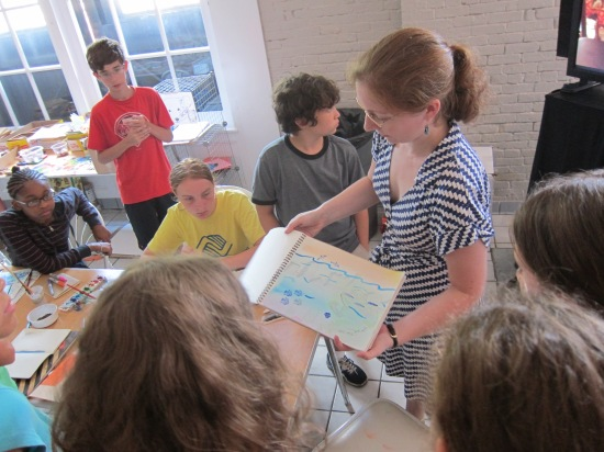 Educator shows group of students a sketchbook with a multimedia drawing/painting of a submerged city and overtaking sealife to express concerns about global warming.