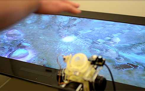 Free air sensations can be delivered to a user that map to a wide range of textures. Here a user can control a virtual character moving over textures such as water and grass. (Photo and caption credit Disney Research, see link above)